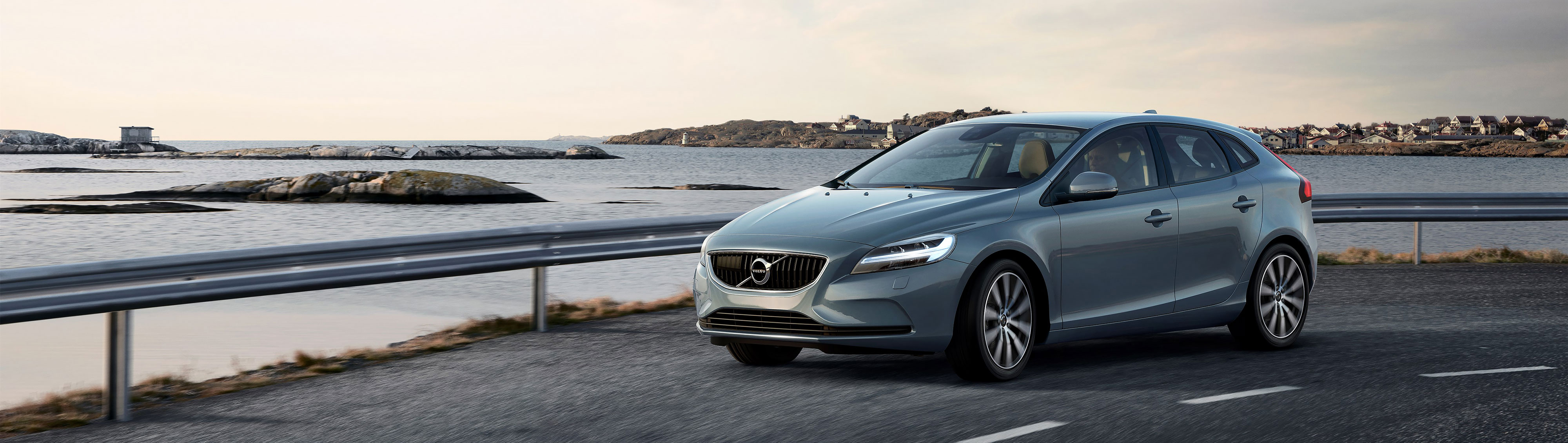 The Volvo V40 in Mussel Blue on a road alongside a body of water