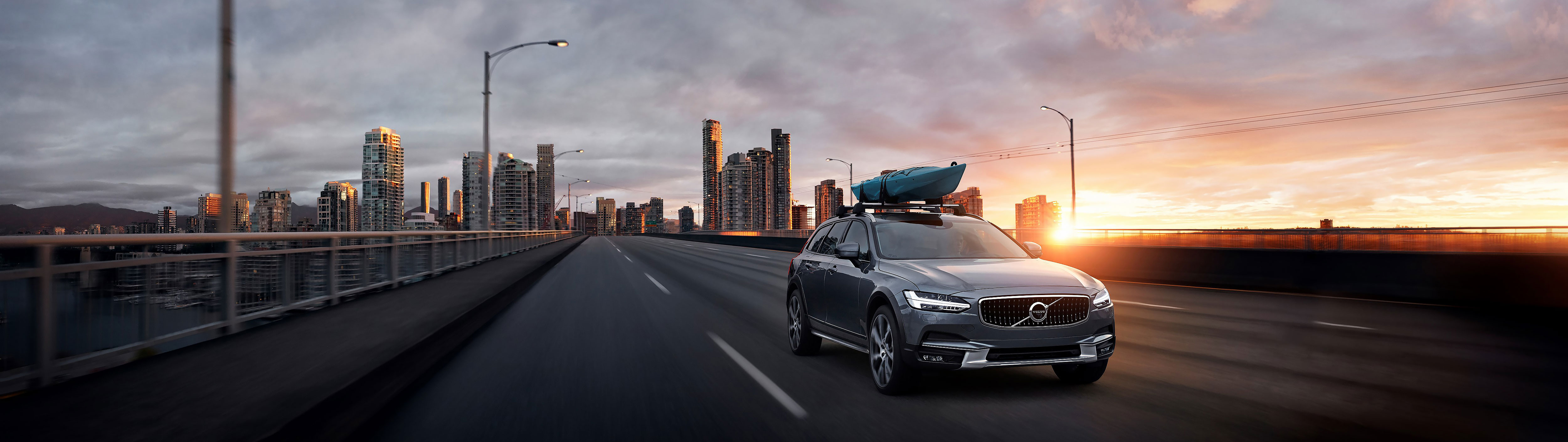 The Volvo V90 Cross Country with kayak strapped to roof, driving away from cityscape