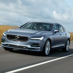 Look at the front of the Volvo S90 while the car drives on the road.
